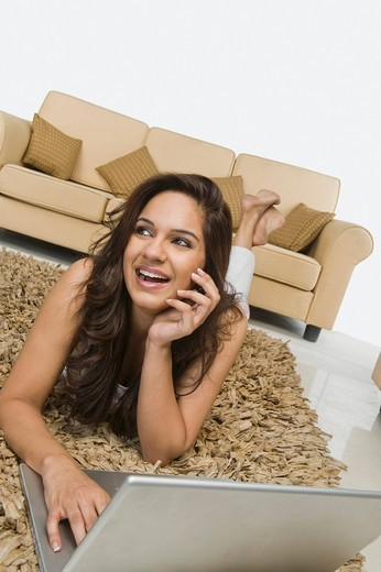 Woman lying on a rug and using a laptop : Stock Photo