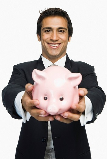 Stock Photo: 1657R-35513 Portrait of a businessman holding a piggy bank