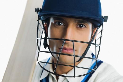 Portrait of a cricket batsman holding a bat : Stock Photo