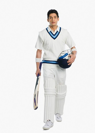 Cricket batsman carrying a bat and a helmet : Stock Photo