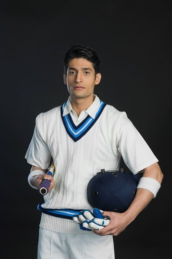 Cricket batsman holding a bat with a helmet and gloves : Stock Photo