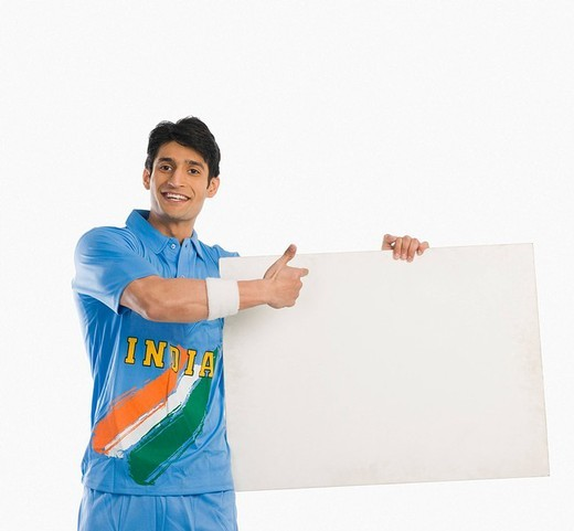 Cricket player pointing at a blank placard and smiling : Stock Photo
