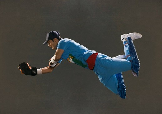 Wicket keeper diving to catch a ball : Stock Photo