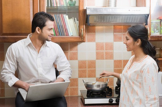 Man working on a laptop while his wife cooking in the kitchen : Stock Photo