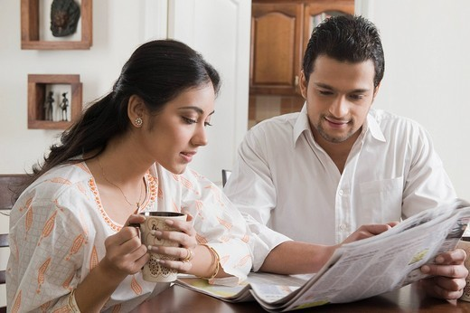 Couple reading a newspaper with cup of coffee : Stock Photo