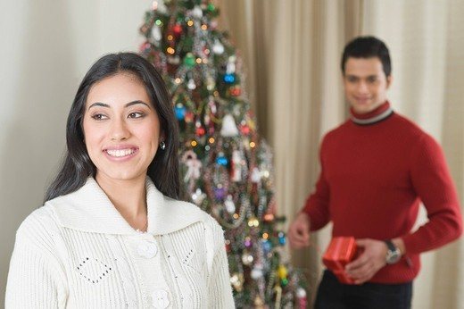 Couple smiling near a Christmas tree : Stock Photo