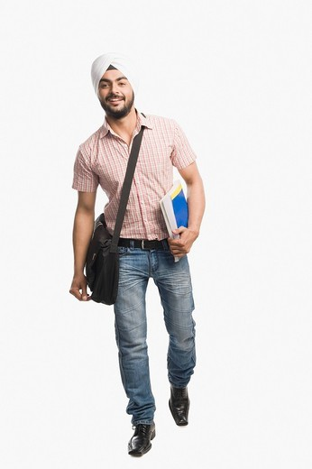 University student holding a book and smiling : Stock Photo