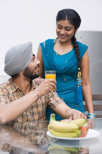 Man drinking orange juice with his wife standing beside him : Stock Photo