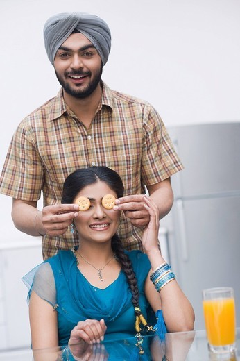 Man covering his wife´s eyes with cookies : Stock Photo