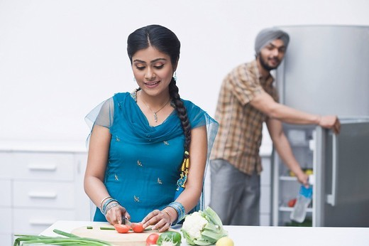 Woman chopping vegetables in the kitchen : Stock Photo