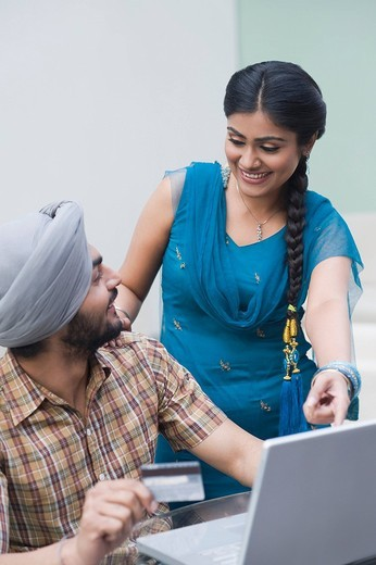 Couple shopping online on a laptop : Stock Photo