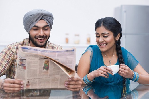 Couple reading a newspaper and smiling : Stock Photo