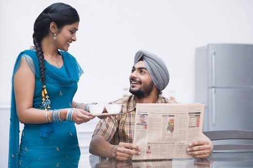 Man reading a newspaper with his wife serving tea : Stock Photo