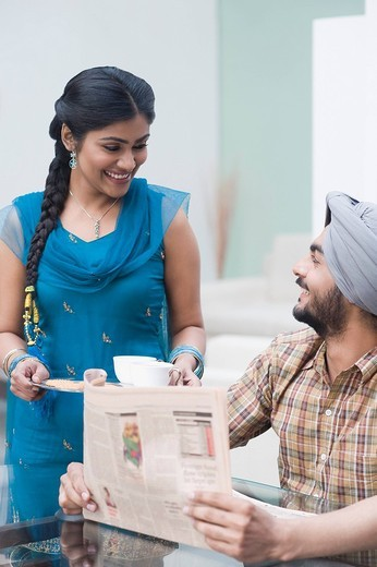 Stock Photo: 1657R-36050 Man reading a newspaper while his wife serving tea