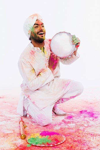 Man playing tambourine on Holi : Stock Photo