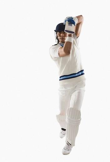 Cricket batsman playing a straight drive shot : Stock Photo