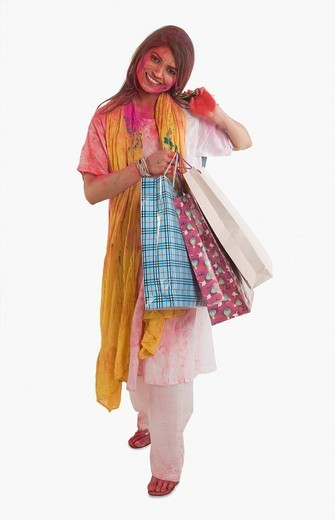 Woman carrying shopping bags on Holi : Stock Photo