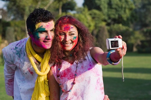 Couple taking a picture of themselves with a camera on Holi : Stock Photo