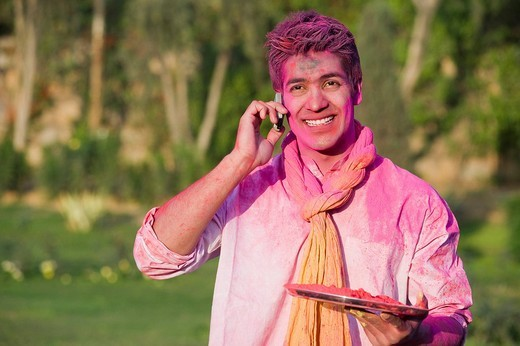 Man celebrating Holi and using a mobile phone : Stock Photo