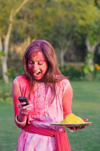 Woman celebrating Holi and text messaging on a mobile phone : Stock Photo