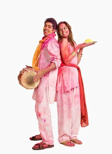 Couple celebrating Holi with colors and a drum : Stock Photo