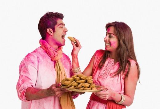 Couple celebrating Holi with plate of gujiyas : Stock Photo