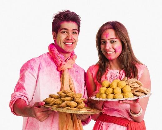 Couple celebrating Holi with plates of sweet foods : Stock Photo