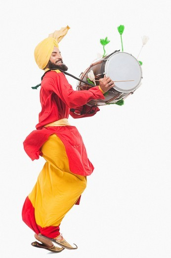 Stock Photo: 1657R-37023 Man performing Bhangra dance with a dholak