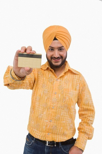 Portrait of a Sikh man showing a credit card : Stock Photo