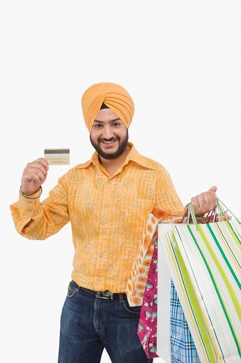 Stock Photo: 1657R-37105 Portrait of a Sikh man carrying shopping bags and showing a credit card