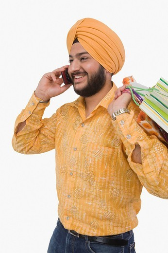Sikh man talking on mobile phone and carrying a shopping bag : Stock Photo