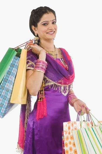 Woman carrying shopping bags and smiling : Stock Photo