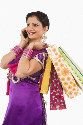 Woman carrying shopping bags and talking on a mobile phone : Stock Photo