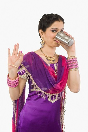 Stock Photo: 1657R-37126 Woman drinking lassi and gesturing