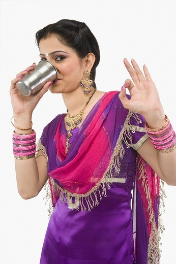 Woman drinking lassi and gesturing : Stock Photo