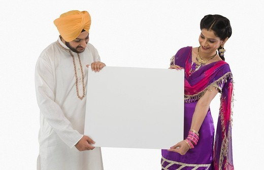Close_up of a Sikh couple holding a blank placard : Stock Photo