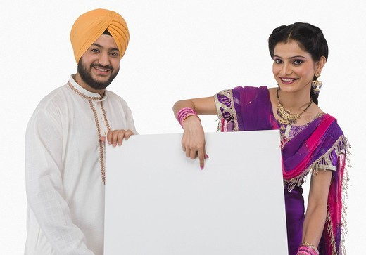Portrait of a Sikh couple showing a blank placard : Stock Photo
