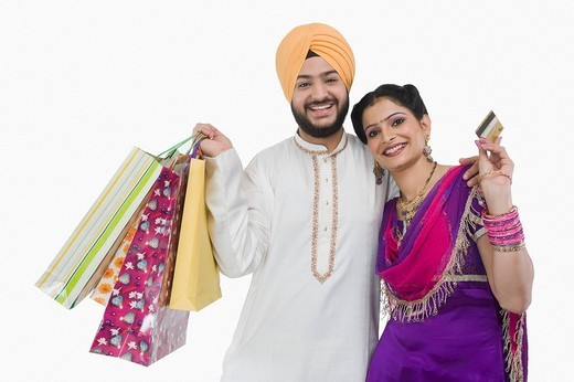 Portrait of a Sikh couple carrying shopping bags and showing a credit card : Stock Photo
