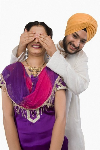 Sikh man covering a woman´s eyes from behind : Stock Photo