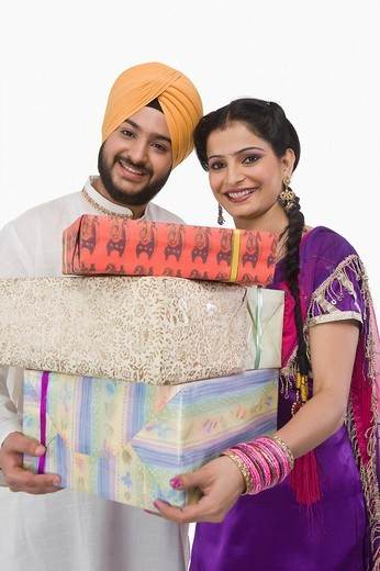 Portrait of a Sikh couple holding gift boxes : Stock Photo