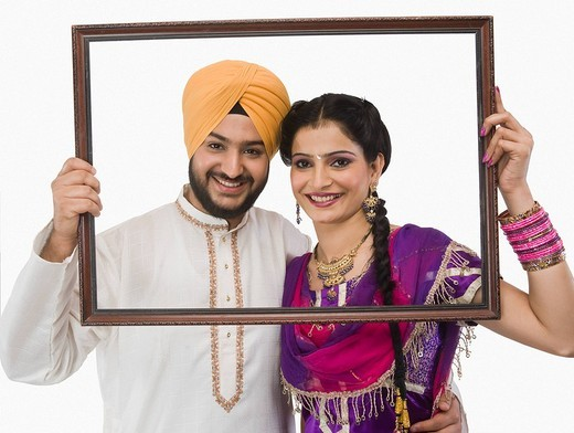 Portrait of a Sikh couple holding a picture frame and smiling : Stock Photo