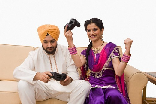 Sikh couple playing video game : Stock Photo