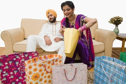 Man resting on a couch and wife checking shopping bags : Stock Photo