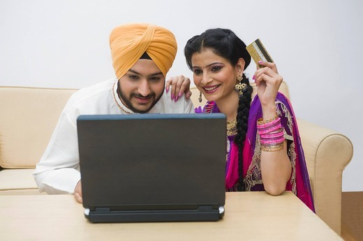 Sikh couple holding a credit card and working on a laptop : Stock Photo