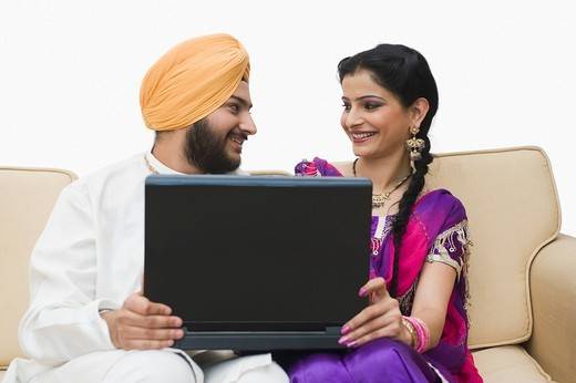 Sikh couple using a laptop : Stock Photo