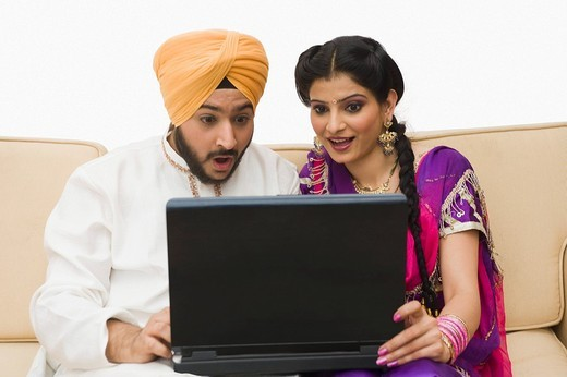 Sikh couple using a laptop : Stock Photo
