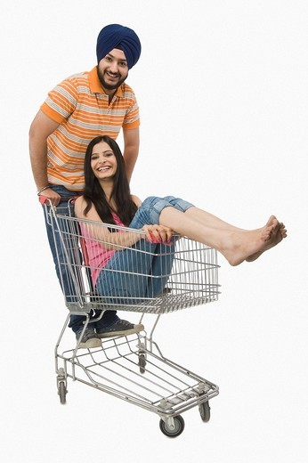 Man pushing a woman sitting on a shopping cart : Stock Photo