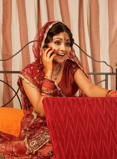 Bride talking on a mobile phone and holding a jewelry box : Stock Photo