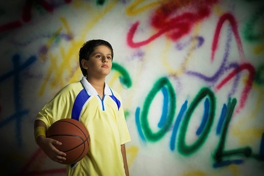 Close_up of a boy holding a basketball : Stock Photo