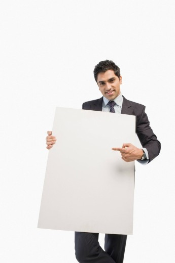 Portrait of a businessman showing a blank placard : Stock Photo